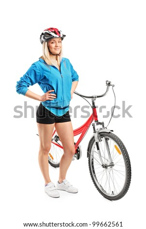 Full length portrait of a female biker with helmet posing next to a bike isolated on white background