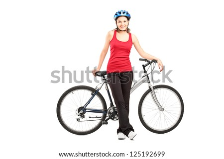 Full length portrait of a female biker with helmet posing next to a mountain bike isolated against white background - stock photo