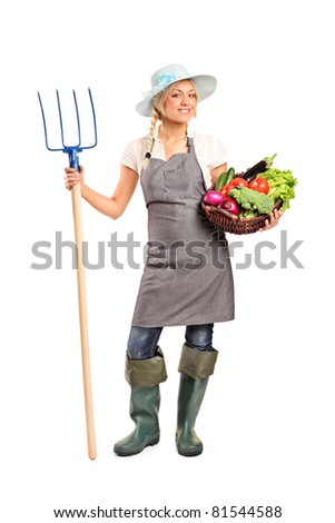 Full length portrait of a female farmer holding a pitchfork and basket with vegetables isolated against white background - stock photo