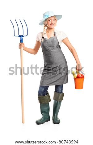 Full length portrait of a female farmer holding a pitchfork and bucket with vegetables isolated on white background - stock photo