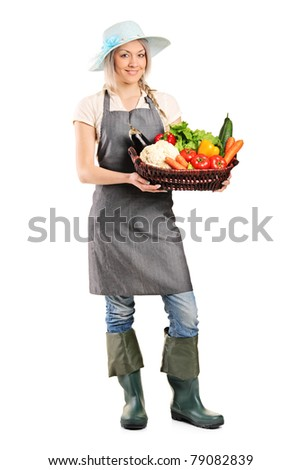 Full length portrait of a female gardener holding a basket of vegetables isolated on white background - stock photo