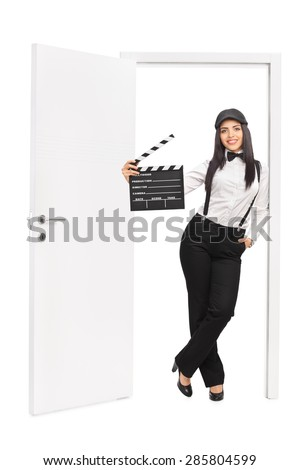 Full length portrait of a female movie director holding a clapperboard and leaning on the frame of an open door isolated on white background - stock photo