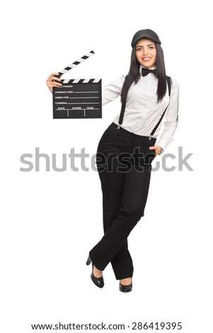 Full length portrait of a female movie director in an artistic outfit and holding a clapperboard isolated on white background - stock photo