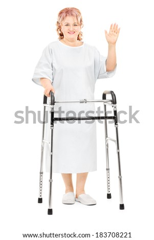 Full length portrait of a female patient with walker waving with hand isolated on white background