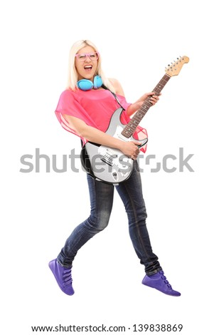 Full length portrait of a female rock star jumping and  playing a guitar, isolated on white background - stock photo