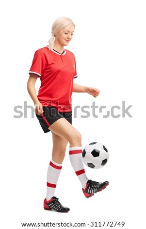Full length portrait of a female soccer player juggling a ball and smiling isolated on white background  - stock photo