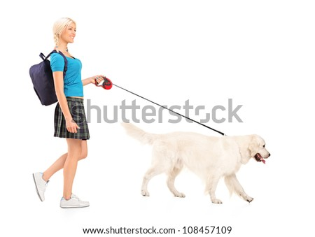 Full length portrait of a female student walking a dog, isolated on white background - stock photo