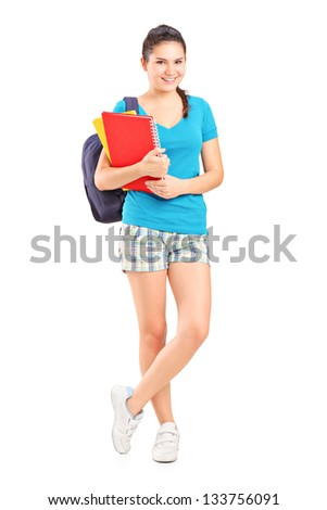 Full length portrait of a female student with backpack holding notebooks isolated on white background