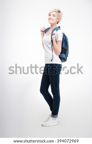 Full length portrait of a female student with backpack standing isolated on a white background - stock photo