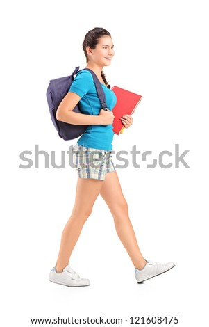 Full length portrait of a female student with backpack walking and holding book isolated on white background - stock photo