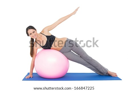 Full length portrait of a fit young woman stretching on fitness ball over white background