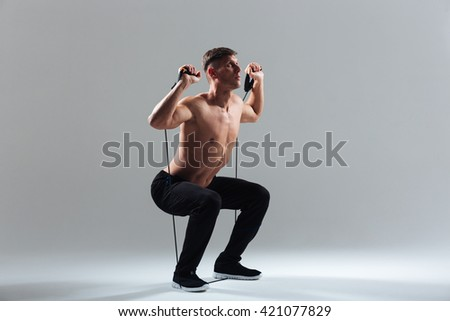 Full length portrait of a fitness man squatting with expander over gray background - stock photo