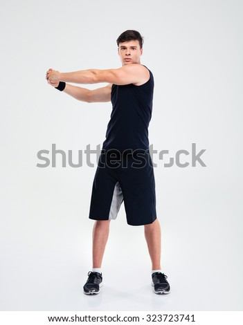 Full length portrait of a fitness man stretching hands isolated on a white background - stock photo