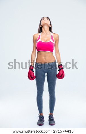 Full length portrait of a fitness woman in boxing gloves looking jup over gray background - stock photo
