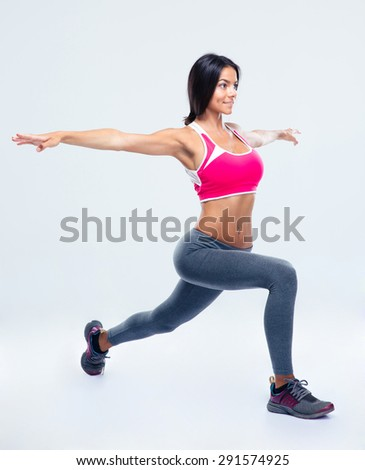 Full length portrait of a fitness woman stretching over gray background - stock photo