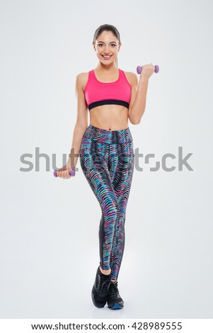 Full length portrait of a fitness woman workout with dumbbells isolated on a white background and looking at camera - stock photo
