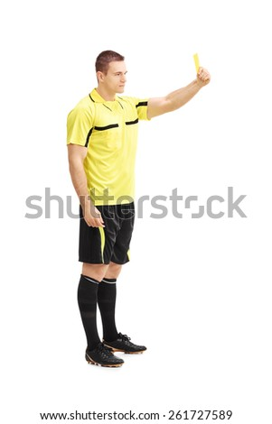 Full length portrait of a football referee showing a yellow card isolated on white background - stock photo