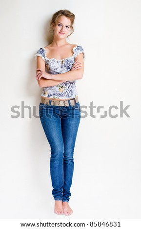 Full length portrait of a friendly, fashionable confident young blond woman. - stock photo
