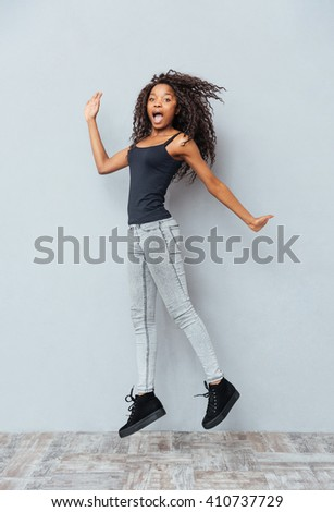 Full length portrait of a funny afro american woman jumping on gray background - stock photo