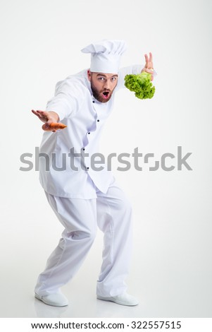 Full length portrait of a funny chef cook dancing isolated on a white background - stock photo