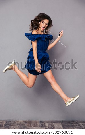 Full length portrait of a funny woman in dress listening music and jumping on gray background