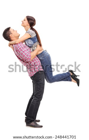 Full length portrait of a girl throwing herself in the arms of her boyfriend isolated on white background - stock photo