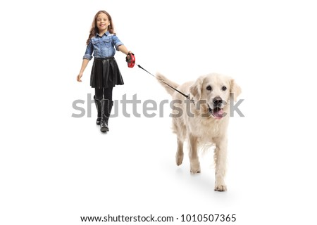 Full length portrait of a girl walking a dog isolated on white background