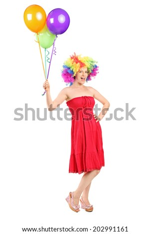 Full length portrait of a girl with wig holding a bunch of balloons isolated on white background - stock photo
