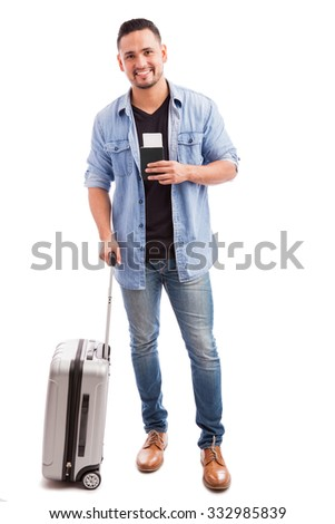 Full length portrait of a good looking guy carrying a suitcase and his passport before going on vacation - stock photo