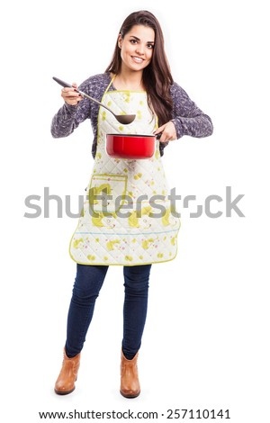 Full length portrait of a good-looking young housewife wearing an apron and cooking lunch - stock photo