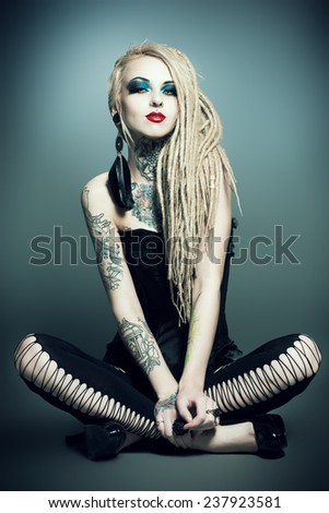 Full length portrait of a gorgeous sexy girl with black make-up and long dreadlocks. Gothic style. Fashion. Cosmetics, hairstyle. Tattoo. - stock photo