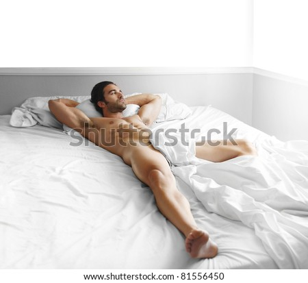 Full length portrait of a gorgeous sexy nude male model laying in bed - stock photo