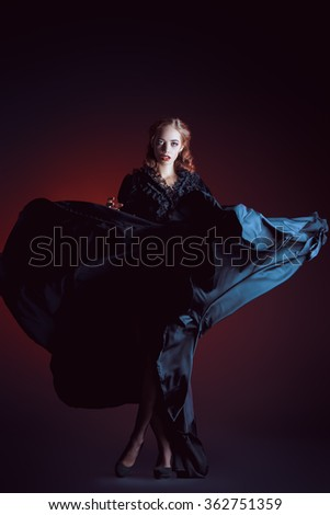 Full length portrait of a gorgeous vampire woman in black medieval dress over dark bloody  background. Halloween.  - stock photo