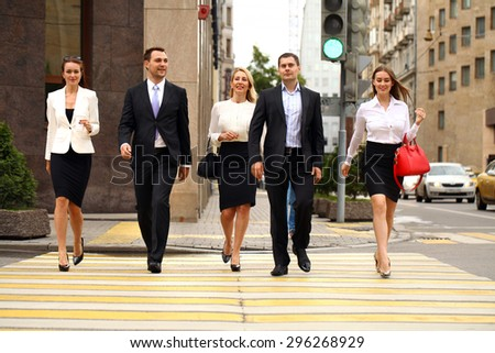 Full length portrait of a Group Of Businesspeople Crossing Summer Street - stock photo