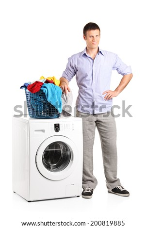 Full length portrait of a guy standing by a washing machine with a laundry basket on it isolated on white background
