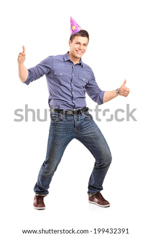 Full length portrait of a guy with party hat giving thumbs up isolated on white background - stock photo