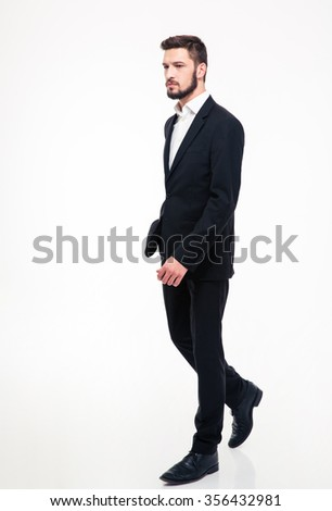 Full length portrait of a handsome businessman walking isolated on a white background
