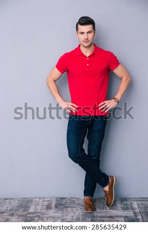 Full length portrait of a handsome man standing over gray background and looking at camera - stock photo