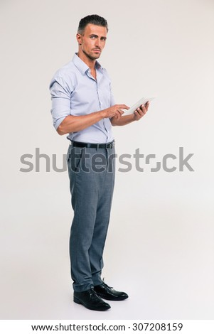 Full length portrait of a handsome man using tablet computer isolated on a white background. Looking at camera - stock photo