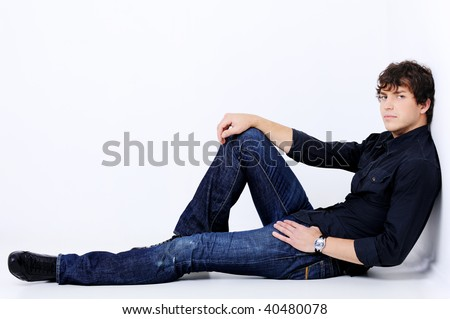 full-length portrait of a handsome sexy man lying and pose in the studio - stock photo