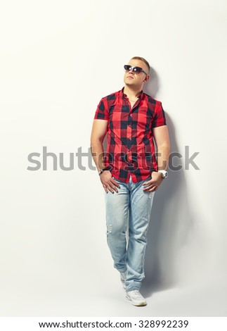 Full length portrait of a handsome stylish man in hipster plaid shirt and sunglasses