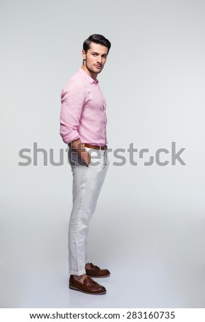 Full length portrait of a handsome young businessman looking at camera over gray background - stock photo