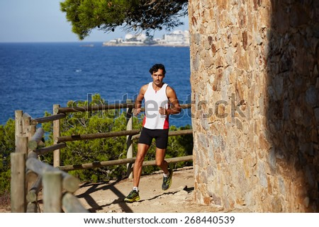 Full length portrait of a handsome young male athlete jogging outdoors with amazing sea horizon on background, jogging athlete over mountain trail on high altitude - stock photo