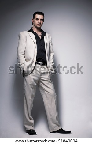 Full length portrait of a handsome young man standing with hishands in the pocket. - stock photo