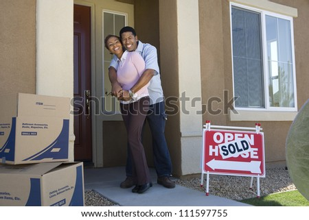 Full length portrait of a happy African American couple embracing each other at doorway