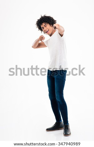 Full length portrait of a happy afro american man pointing fingers at camera isolated on a white background