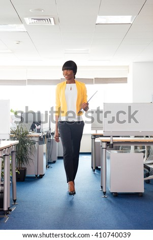 Full length portrait of a happy afro american woman walking in office - stock photo
