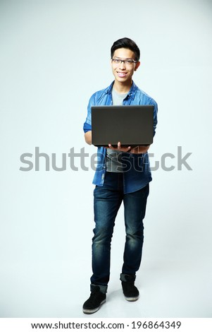 Full length portrait of a happy asian man standing with laptop on gray background - stock photo