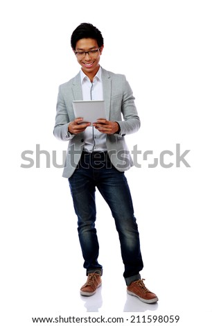 Full length portrait of a happy asian man using tablet computer over white background - stock photo