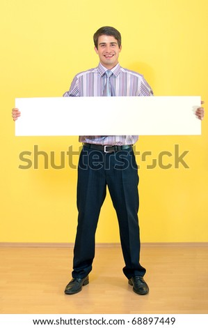 full length portrait of a happy attractive young business man holding wide blank white card against uniform background